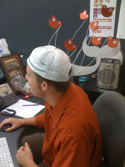 A man sitting at a computer wearing a hat that looks like the Twitter Fail Whale