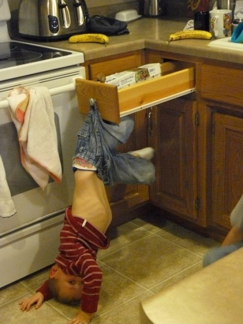 Kid hanging from a drawer